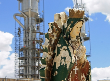 A natural gas processing plant outside of Bloomfield, New Mexico, has virtually swallowed up a Catholic cemetery. Virgen de Guadalupe with men working on distilling columns.